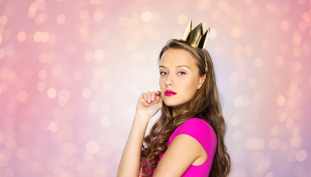 people, holidays and fashion concept - young woman or teen girl in pink dress and princess crown over rose quartz and serenity lights background