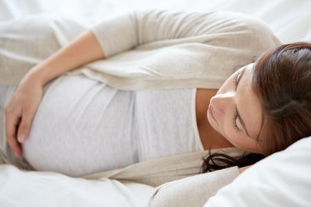 pregnancy, rest, people and expectation concept - pregnant woman sleeping in bed at home Stock Photo