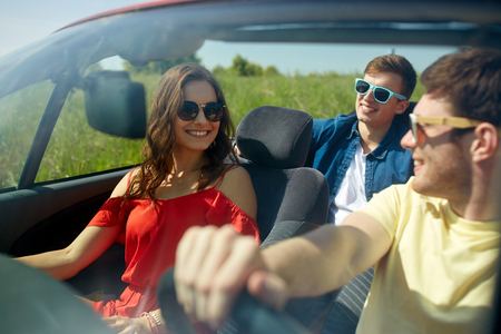 suburban: leisure, road trip, travel and people concept - happy friends driving in cabriolet car along country road