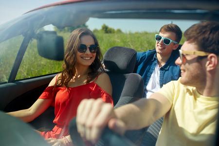 ocio, viaje por carretera, los viajes y el concepto de la gente - amigos felices que conducen en coche descapotable a lo largo de la carretera nacional Foto de archivo