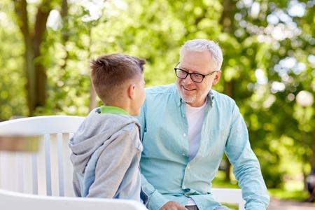 가족, 세대, 커뮤니케이션 및 사람들이 개념 - 행복 할아버지와 손자 여름 공원에서 이야기 스톡 콘텐츠