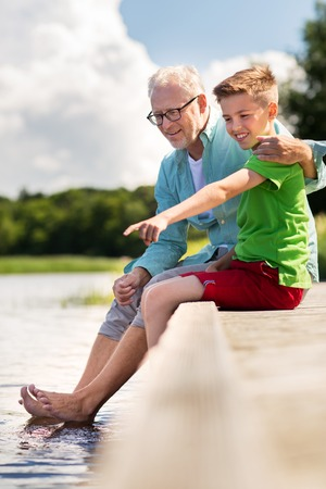 little boys: family, generation, communication and people concept - happy grandfather and grandson sitting on river berth