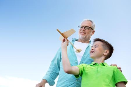 familie, generatie, toekomst, droom en mensen concept - happy grootvader en kleinzoon met speelgoed vliegtuig over de blauwe hemel