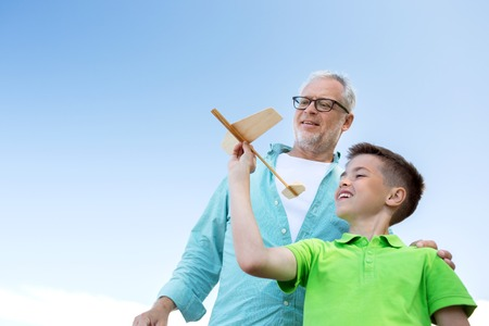 grandkids: family, generation, future, dream and people concept - happy grandfather and grandson with toy airplane over blue sky
