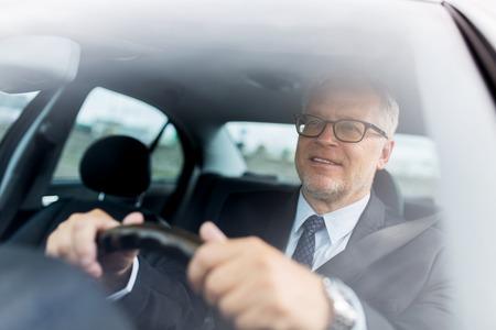 transport, business trip and people concept - happy senior businessman driving car Reklamní fotografie