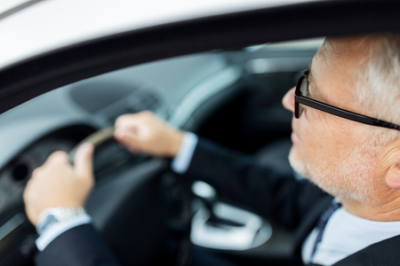 driver: transport, business trip and people concept - happy senior businessman driving car Stock Photo