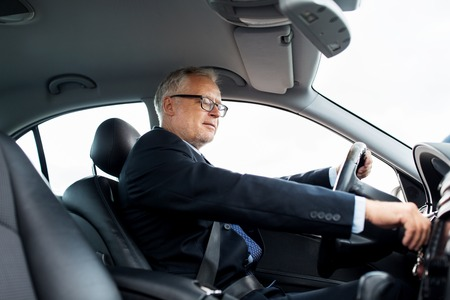 transport, business trip and people concept - happy senior businessman starting car and driving Reklamní fotografie