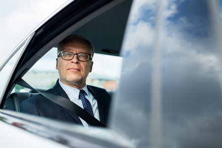 back seat: transport, business trip, safety and people concept - senior businessman driving on car back seat Stock Photo