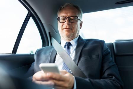taxi: Transporte, viaje de negocios, tecnología y concepto de la gente - hombre de negocios de alto nivel de mensajes de texto en el teléfono inteligente y la conducción en el asiento trasero del coche Foto de archivo