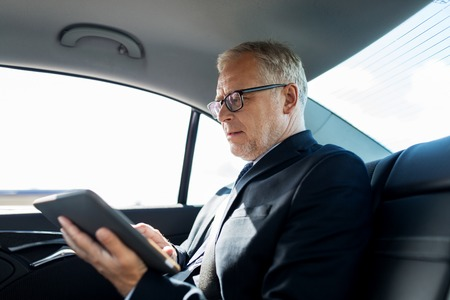 transport, business trip, technology and people concept - senior businessman with tablet pc computer driving on car back seat Standard-Bild