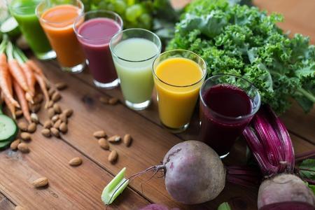 una sana alimentazione, bevande, dieta e il concetto di disintossicazione - bicchieri con diversi succhi di frutta o di verdura e cibo sul tavolo