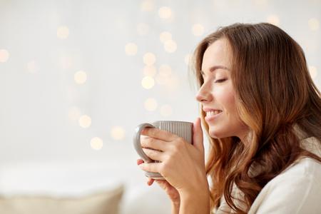 아침, 레저, 크리스마스, 겨울과 사람들이 개념 - 집에서 커피 또는 차 한잔에 행복 한 젊은 여자
