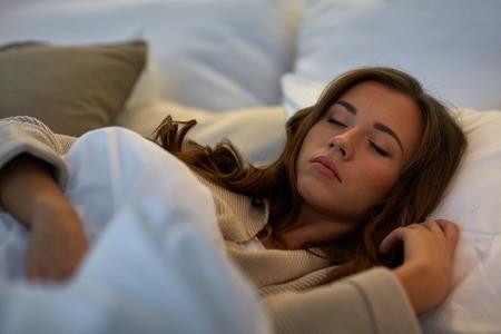 夜、残りの部分、快適さと人々 のコンセプト - 自宅のベッドで寝ている若い女性