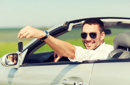 auto business, transport, leisure and people concept - happy man in cabriolet showing car key