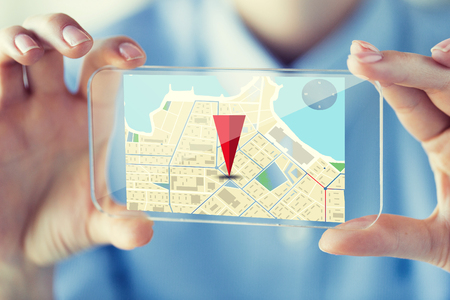 gprs: business, technology, navigation, location and people concept - close up of woman hand holding and showing transparent smartphone with gps navigator map on screen at office