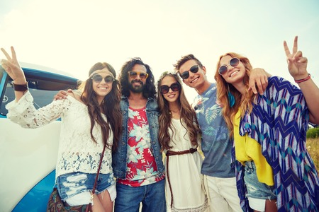 trip over: summer holidays, road trip, vacation, travel and people concept - smiling young hippie friends over minivan car showing peace hand sign Stock Photo