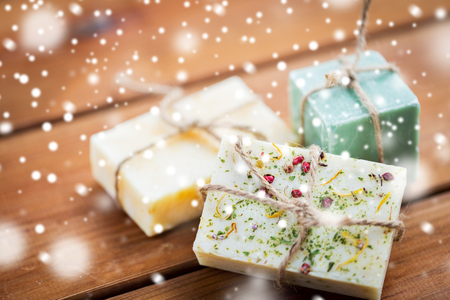 spa beauty: beauty, spa, bodycare, bath and natural cosmetics concept -handmade soap bars on wooden table over snow