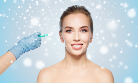 anti season: people, cosmetology, plastic surgery and beauty concept - beautiful young woman face and beautician hand in glove with syringe making injection over blue background and snow
