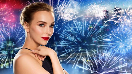 femme fatale: people, holidays, luxury and fashion concept - beautiful woman in black with red lips over night city firework background