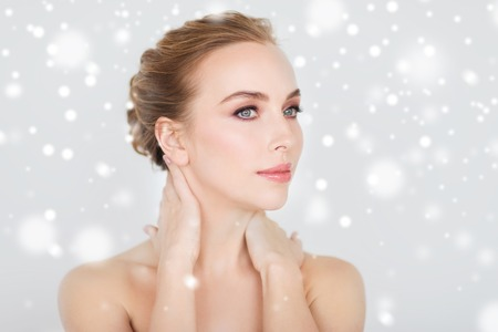 skin beauty: beauty, people, winter and bodycare concept - beautiful young woman face and hands over gray background and snow
