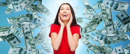 Finanzen, Glück, Emotionen und Menschen Konzept - erstaunt lachen junge Frau im roten Kleid über Geld regen und blauem Hintergrund