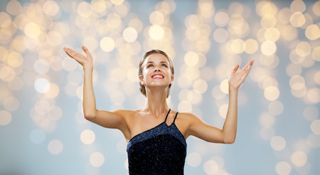 woman hands up: people, happiness, holidays and glamour concept - smiling woman raising hands and looking up over lights background Stock Photo