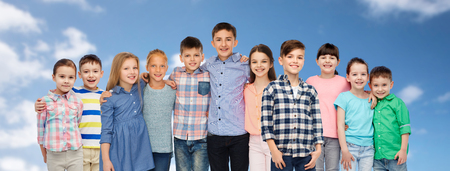 casual clothing: childhood, fashion, friendship and people concept - group of happy smiling children hugging over blue sky and clouds background