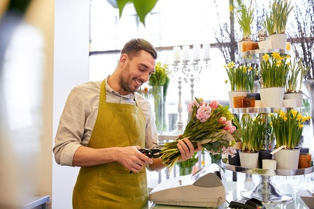 cropping: people, business, sale and floristry concept - happy smiling florist man making bunch and cropping stems by scissors at flower shop Stock Photo