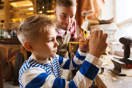 family, carpentry, woodwork and people concept - father and little son with ruler and pencil measuring wood plank at workshop Stock Photo