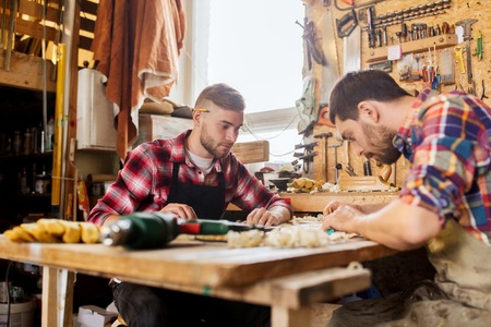 chippy: profession, carpentry, woodwork and people concept - two carpenters with ruler and blueprint at workshop