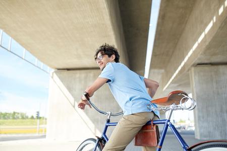 clavados: personas, estilo, ocio y estilo de vida - hombre inconformista joven montar en bicicleta de piñón fijo en la calle de la ciudad Foto de archivo