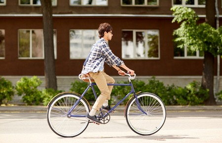 people, style, leisure and lifestyle - young hipster man with shoulder bag riding fixed gear bike on city street Stock Photo