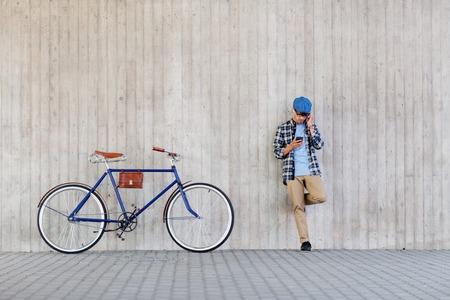 사람, 스타일, 기술, 레저, 라이프 스타일 - 젊은 힙합 남자 스마트 폰 및 도시 거리 벽에서 음악을 듣고 고정 된 기어 자전거 이어폰에서
