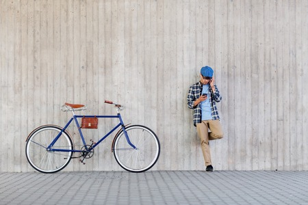 people, style, technology, leisure and lifestyle - young hipster man in earphones with smartphone and fixed gear bike listening to music at city street wall