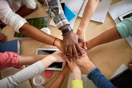manos juntas: educación, escuela, trabajo en equipo y concepto de la gente - cerca de los estudiantes internacionales con las manos en la parte superior de uno al otro sentado en la mesa Foto de archivo