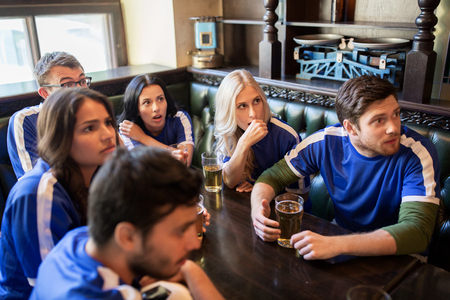 sports bar: people, leisure and sport concept - worried friends or football fans drinking beer and watching soccer game or match at bar or pub Stock Photo
