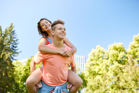 young boys: holidays, vacation, love and people concept - happy smiling teenage couple having fun at summer park