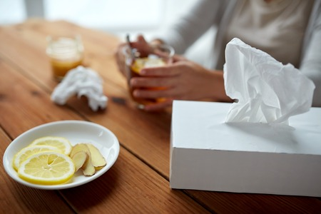 indigenous medicine: health, traditional medicine and ethnoscience concept - ill woman drinking tea with lemon, honey and ginger and paper wipes box on wooden table