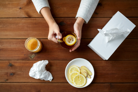 ginger health: health, traditional medicine and ethnoscience concept - ill woman drinking tea with lemon, honey and ginger and paper wipes box on wooden table