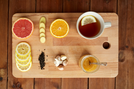 indigenous medicine: health, traditional medicine, folk remedy and ethnoscience concept - cup of ginger tea with honey, citrus and garlic on wooden board Stock Photo