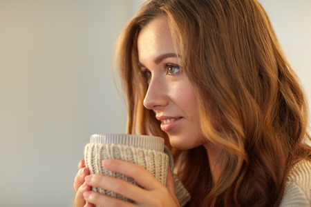 tea cosy: leisure, drink, winter and people concept - close up of happy young woman with cup of coffee or tea at home Stock Photo