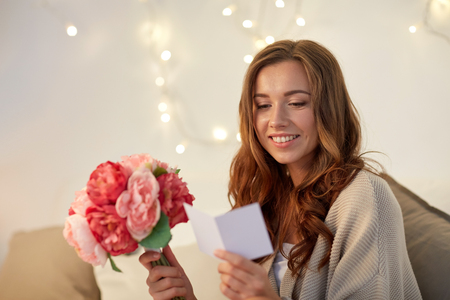 personas saludandose: holidays, winter, birthday and people concept - happy young woman with flowers reading greeting card in bed at home bedroom Foto de archivo