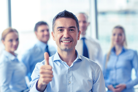 young entrepreneurs: business, teamwork, people, gesture and technology concept - smiling business team showing thumbs up in office Stock Photo