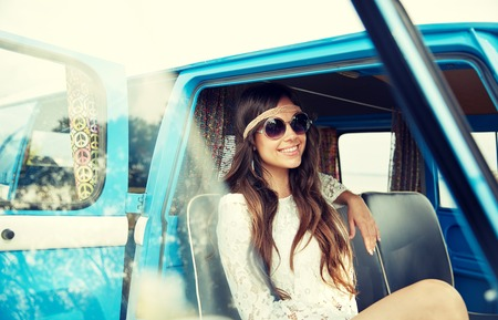 summer holidays, road trip, vacation, travel and people concept - smiling young hippie women in minivan car Stock Photo