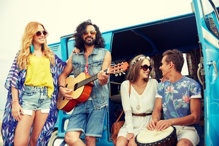trip over: summer holidays, road trip, vacation, travel and people concept - happy young hippie friends with guitar and tom-tom drum playing music over minivan car