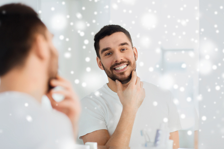 the well groomed: beauty, hygiene, shaving and people concept - smiling young man looking to mirror at home bathroom over snow