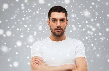 gens, hiver et Noël concept - jeune homme aux bras croisés sur la neige sur fond gris