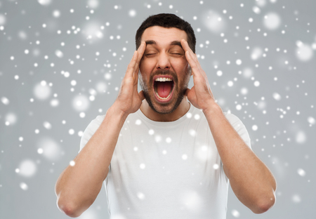 emotions, stress, winter, christmas and people concept - crazy shouting man in t-shirt over snow on gray background