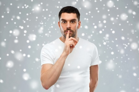 silence, gesture, winter, christmas and people concept - young man making hush sign over gray background