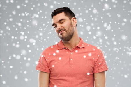 wry: emotion, winter, christmas and people concept - young wrying man over snow on gray background